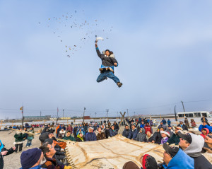 COMPOSITE: (sky added). The Blanket toss concludes the days outside activities for the Nalukatuk festival in Barrow, Alaska, which celebrates the Inupiaq subsistence whale hunt.